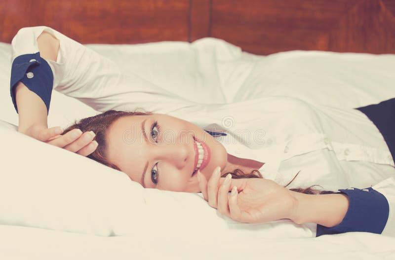 Femme gaie se trouvant sur le lit à la maison rêvassant le repos photographie stock libre de droits