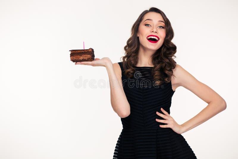 Femme gaie tenant le morceau de gâteau d'anniversaire de chocolat avec la bougie photo libre de droits