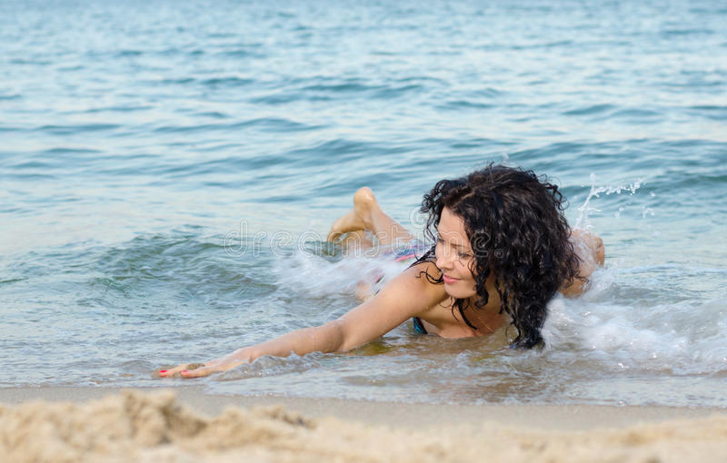 Femme gambadant dans la vague déferlante photos stock