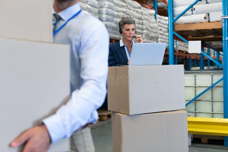 Femme gestionnaire parlant sur un casque pendant qu'elle travaille sur un ordinateur portable dans un entrepôt photos stock
