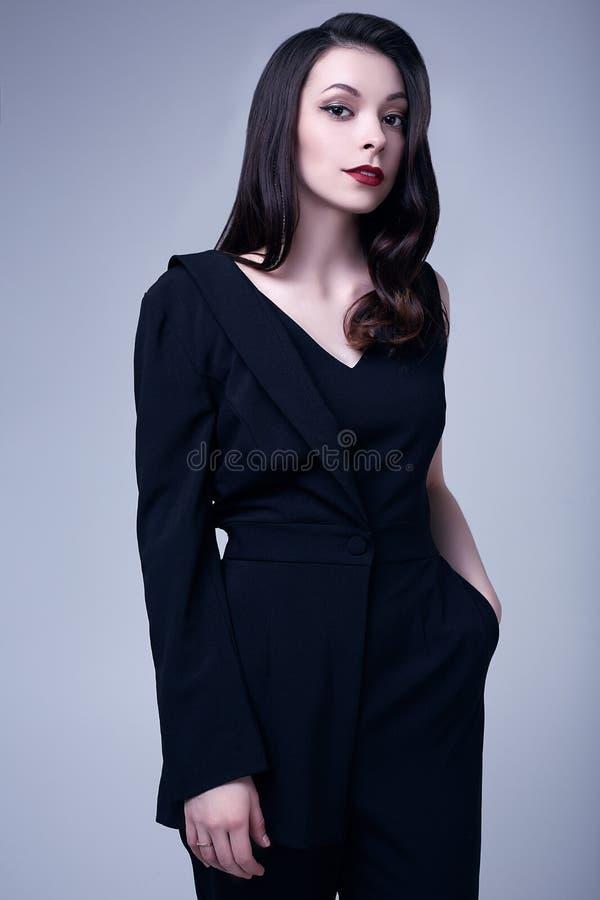 Femme gothique élégante de brune avec les lèvres rouges dans le costume noir photo stock