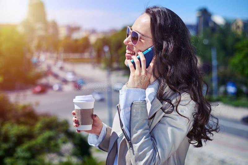 Femme gracieuse parlant au téléphone tout en buvant du café photos stock