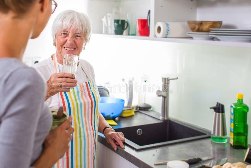 Femme/grand-mère supérieures faisant cuire dans une cuisine moderne avec sa petite-fille photographie stock libre de droits