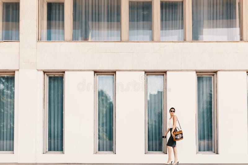 Femme grande à la mode d'affaires dans des lunettes de soleil marchant près d'un bui photographie stock