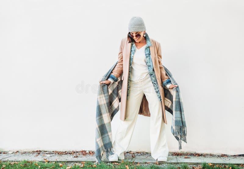Femme habillée dans l'équipement multicouche d'automne : manteau de chameau, denim j photographie stock