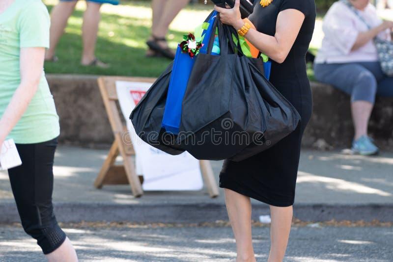 Femme habillée dans la robe noire tenant beaucoup de sacs image libre de droits