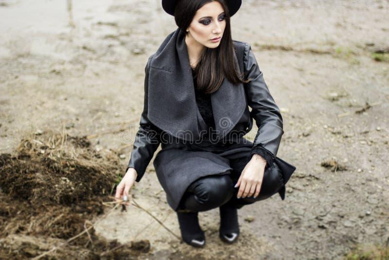 Femme habillée dans le manteau et le chapeau noir photos libres de droits