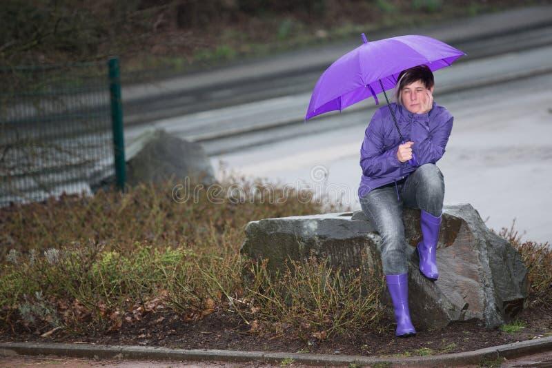 Femme habillée par imperméable attendant sous la pluie images stock