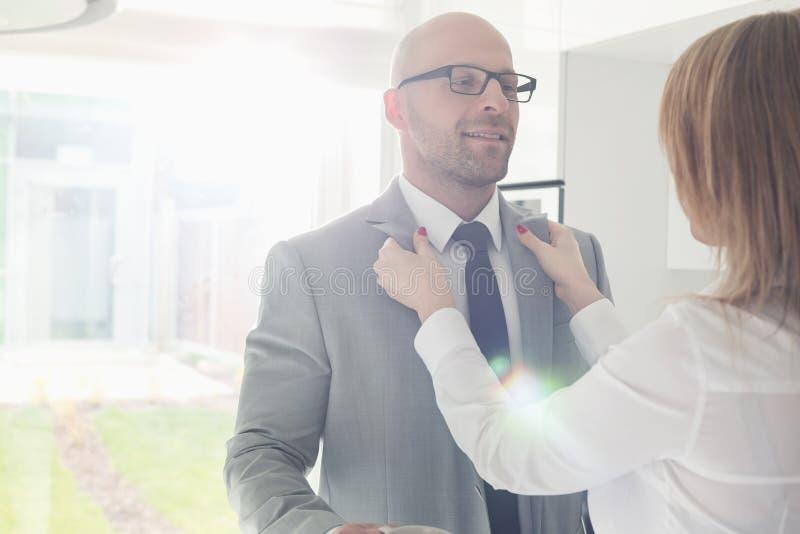 Femme habillant l'homme d'affaires à la maison image libre de droits