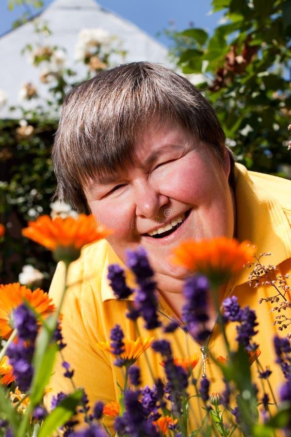 Femme handicapé se trouvant sur l'herbe et l'odeur sur des fleurs image stock