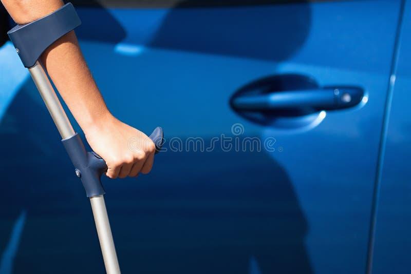 Femme handicapée avec la porte d'ouverture de béquilles d'une voiture image libre de droits