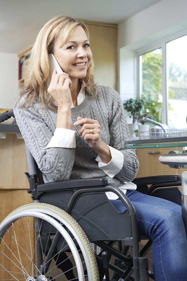 Femme handicapée dans le fauteuil roulant faisant l'appel au téléphone portable à la maison image libre de droits