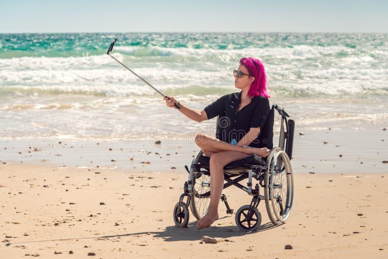 Femme handicapée dans le fauteuil roulant prenant des photos de selfie photo libre de droits