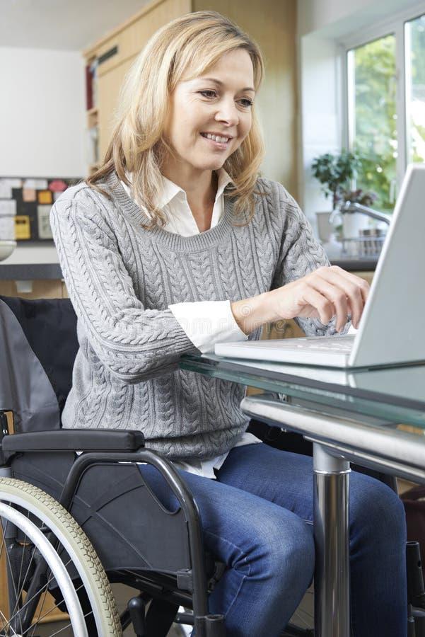 Femme handicapée dans le fauteuil roulant utilisant l'ordinateur portable à la maison photographie stock libre de droits