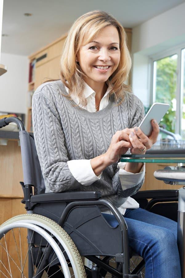 Femme handicapée dans le service de mini-messages de fauteuil roulant au téléphone portable à la maison photos libres de droits