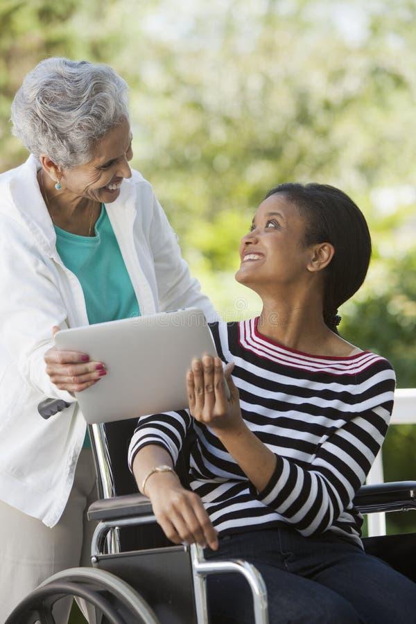 Femme handicapée dans un fauteuil roulant avec sa mère images stock