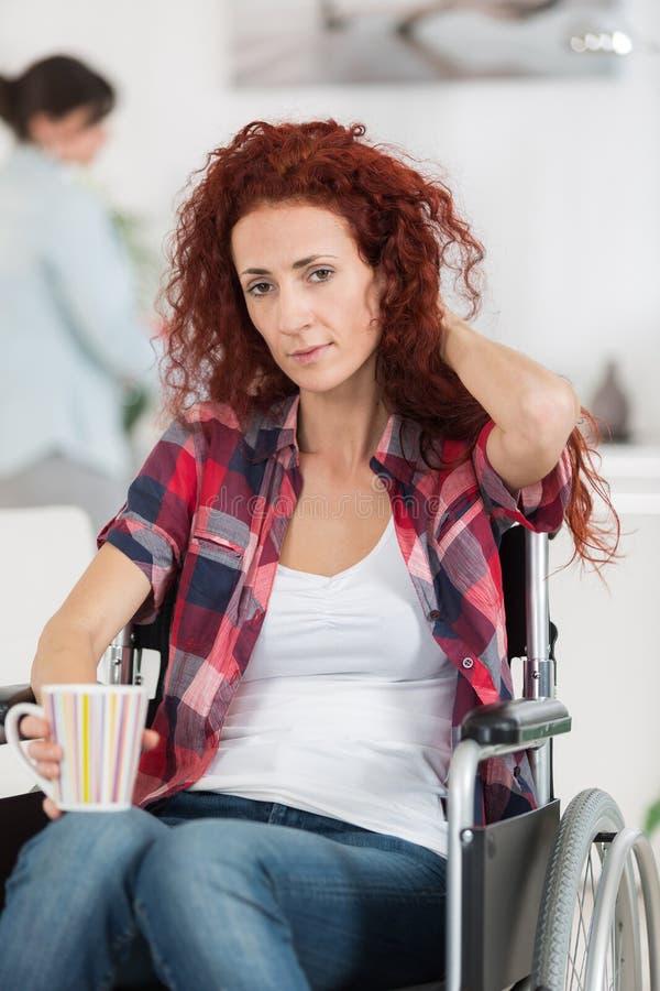 Femme handicapée gaie tenant la tasse de café chaude à la maison photo stock