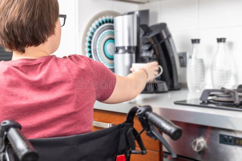 Femme handicapée obtenant le café dans la cuisine photos stock