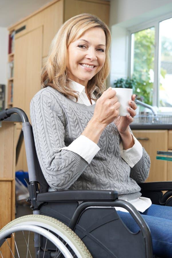 Femme handicapée s'asseyant dans le fauteuil roulant à la maison avec la boisson chaude image stock
