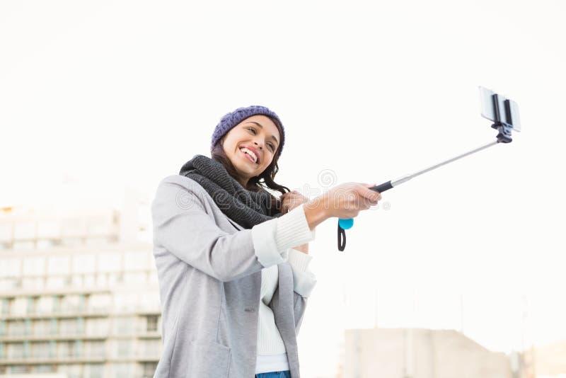 Femme heureuse à l'aide du bâton de selfie photos stock