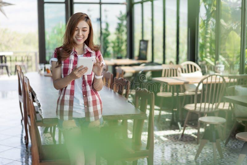 Femme heureuse à l'aide du comprimé numérique en café image libre de droits