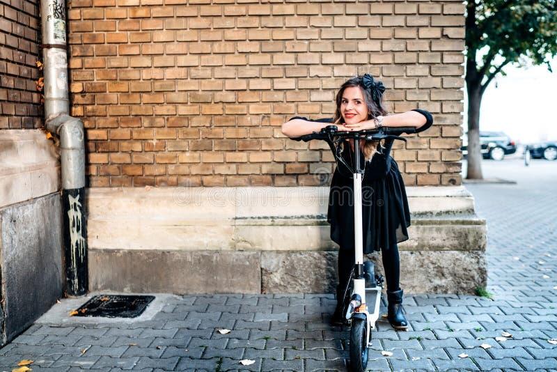 Femme heureuse à l'aide du scooter de coup-de-pied dans la ville - portrait contre le mur de briques de vintage photo stock