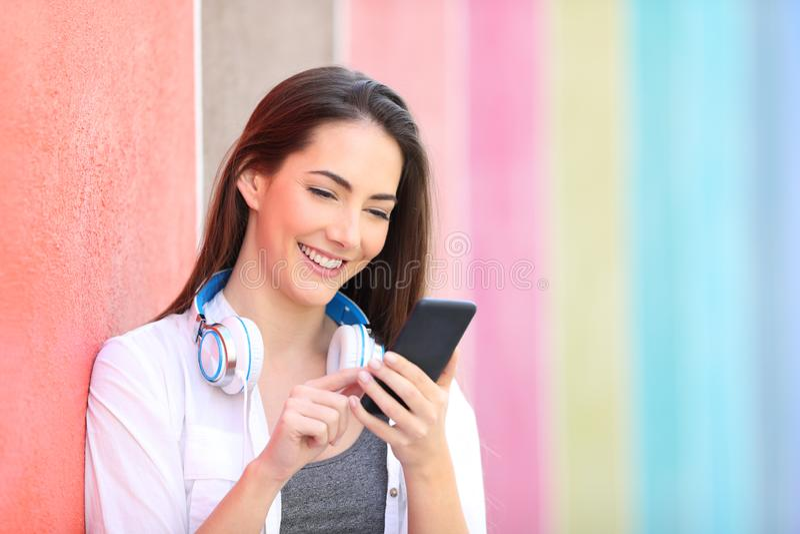 Femme heureuse ? l'aide du t?l?phone intelligent se penchant dans un mur photo libre de droits
