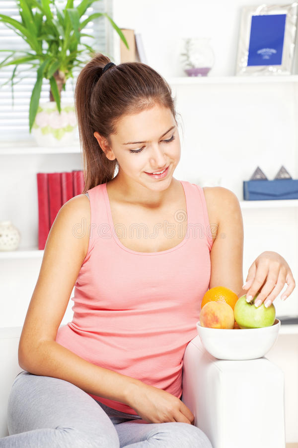 Femme heureuse à la maison sur le sofa avec des fruits image stock
