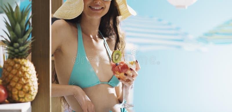 Femme heureuse à la plage mangeant d'une salade de fruits images stock