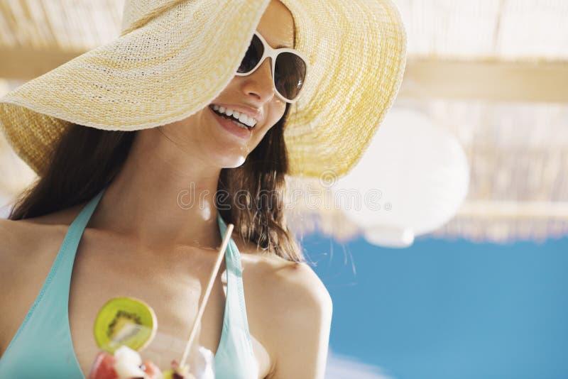 Femme heureuse à la plage mangeant d'une salade de fruits image stock