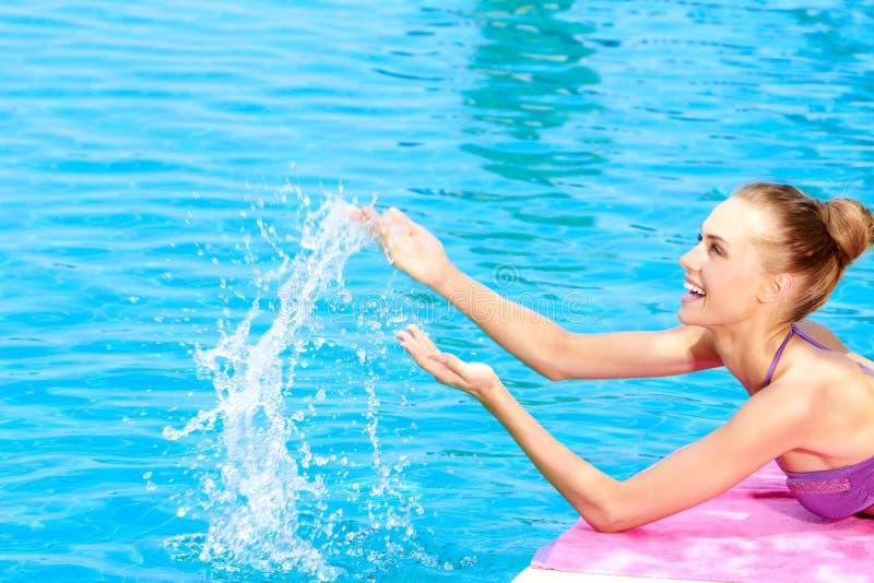 Femme heureuse éclaboussant l'eau dans une piscine photographie stock libre de droits