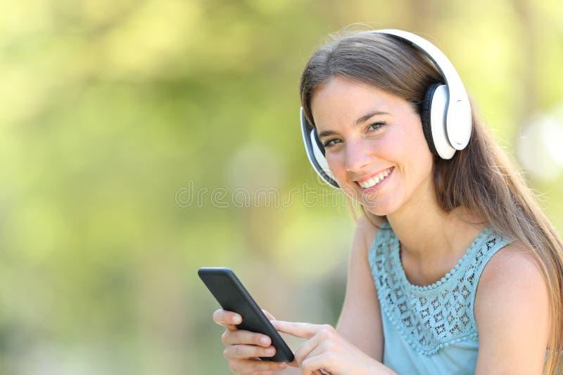 Femme heureuse écoutant la musique tenant le téléphone intelligent photos stock