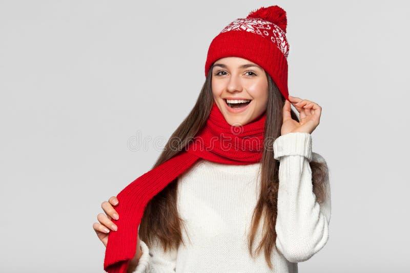 Femme heureuse étonnée dans l'excitation Fille de Noël utilisant le chapeau tricoté et l'écharpe chauds, d'isolement sur le fond  photos stock