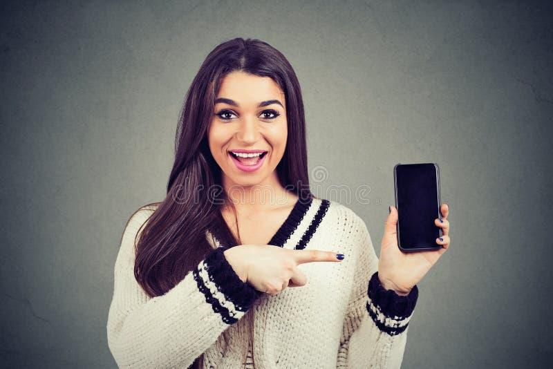 Femme heureuse étonnée dans le chandail montrant le pointage à l'écran vide de smartphone photo stock
