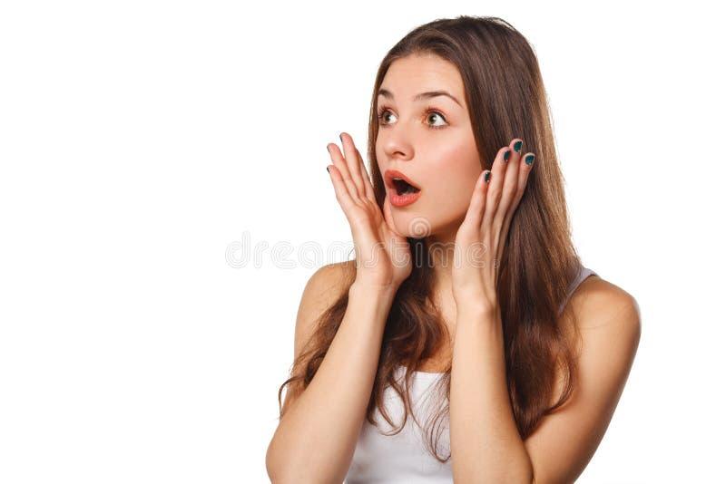 Femme heureuse étonnée regardant en longueur dans l'excitation, d'isolement sur le fond blanc images stock
