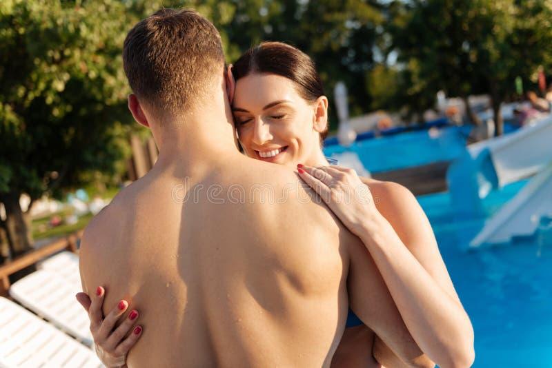 Femme heureuse étreignant son mari à la station de vacances photographie stock libre de droits