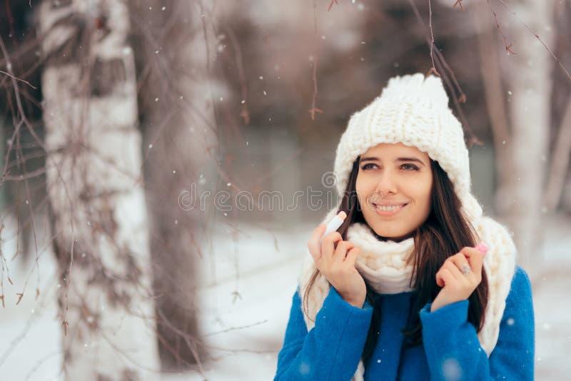 Femme heureuse appliquant le baume à lèvres dehors en hiver photos stock