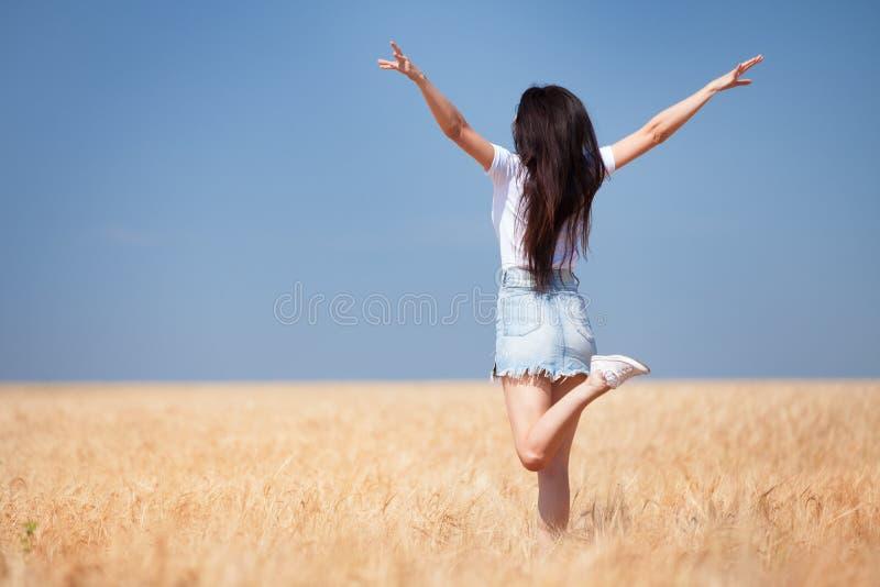 Femme heureuse appr?ciant la vie dans la beaut? de nature de champ, le ciel bleu et le domaine avec du bl? d'or Style de vie ext? photo libre de droits
