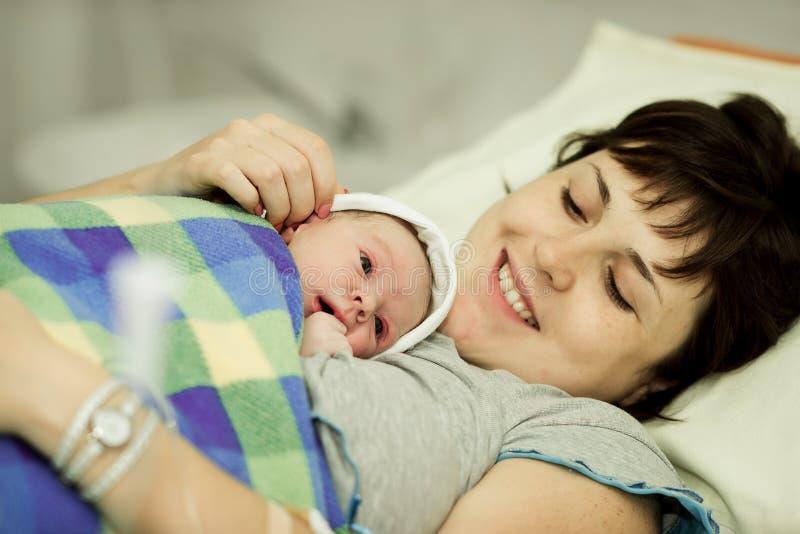 Femme heureuse après naissance avec un bébé nouveau-né photos stock