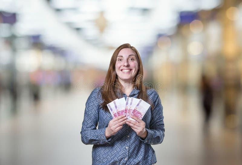 Femme heureuse assez jeune d'affaires prenant beaucoup d'argent au-dessus de bleu photos libres de droits