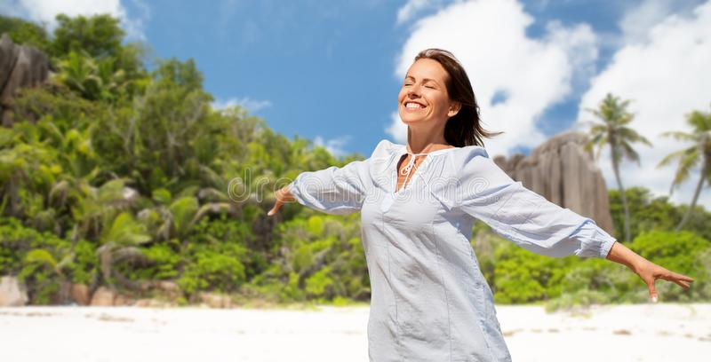 Femme heureuse au-dessus de plage tropicale d'île des Seychelles image libre de droits