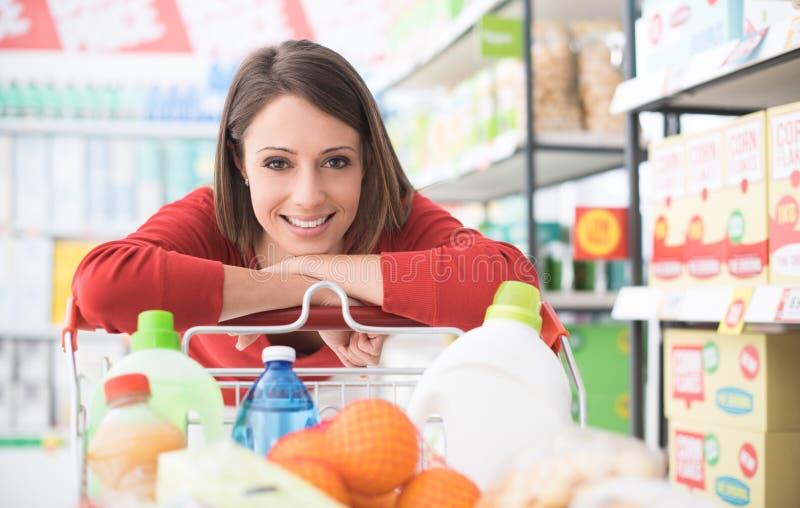 Femme heureuse au supermarché image stock