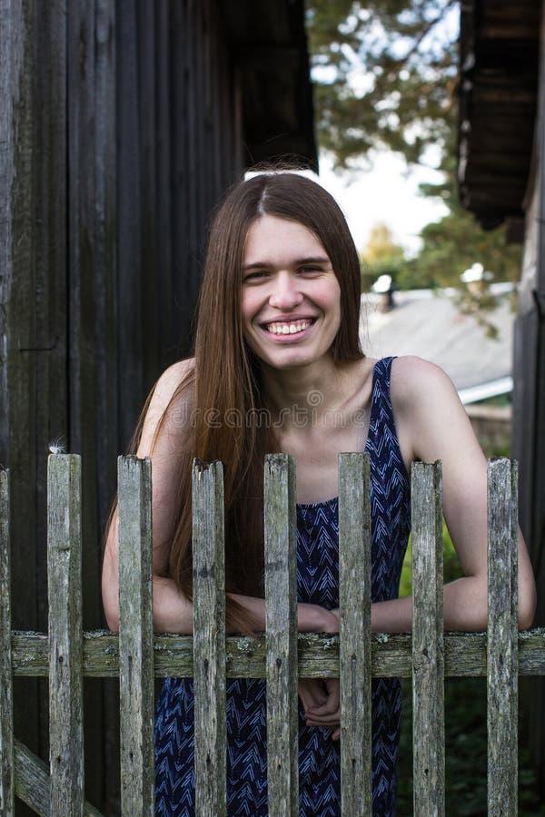 Femme heureuse avec de longs cheveux bruns près des barrières en bois dans le village image libre de droits