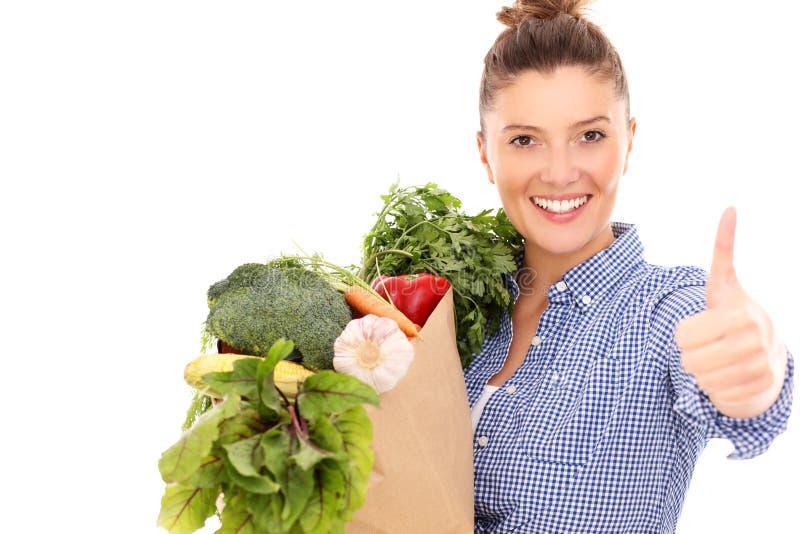 Femme heureuse avec des légumes montrant correct image libre de droits