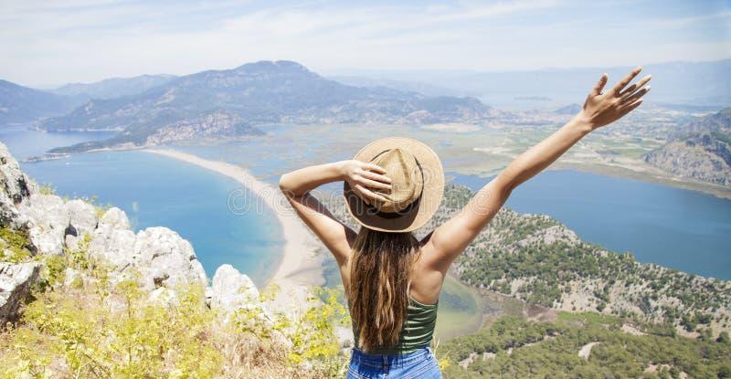 Femme heureuse avec des mains vers le haut de la position sur la falaise au-dessus de la mer et des îles à l'été Humeur de cru, c photo stock