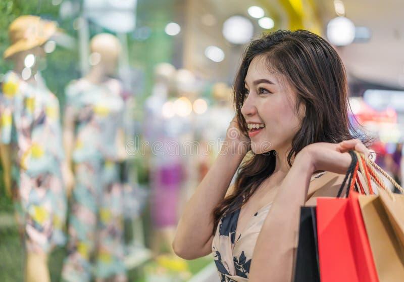 Femme heureuse avec des paniers dans le magasin de vêtements photo stock