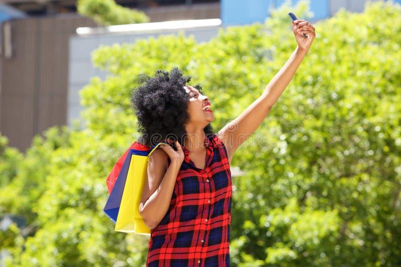 Femme heureuse avec des paniers prenant le selfie dehors images libres de droits