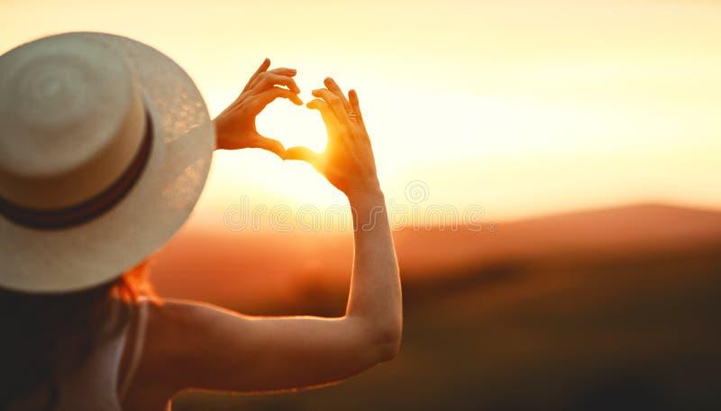 Femme heureuse avec des paumes de vos doigts dans la forme d'un coeur sur le coucher du soleil en nature images libres de droits