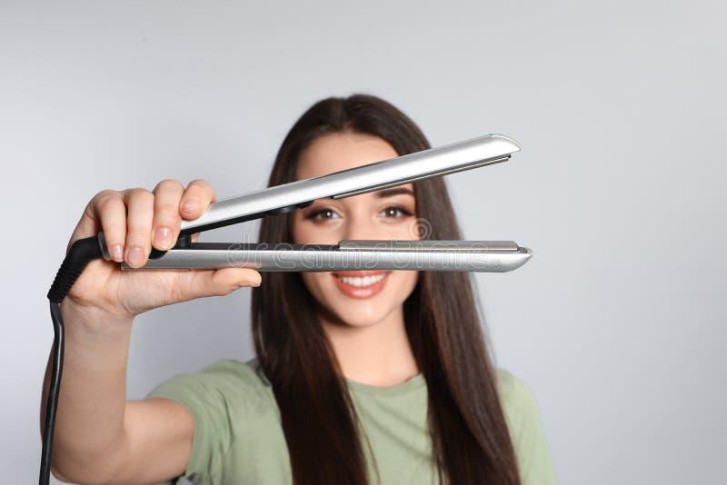 Femme heureuse avec du fer de cheveux photos libres de droits