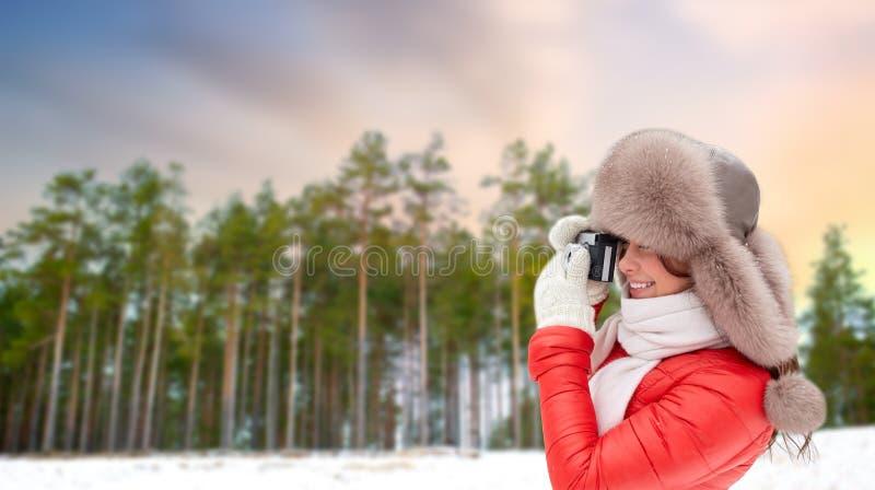 Femme heureuse avec l'appareil-photo de film au-dessus de la forêt d'hiver photos stock